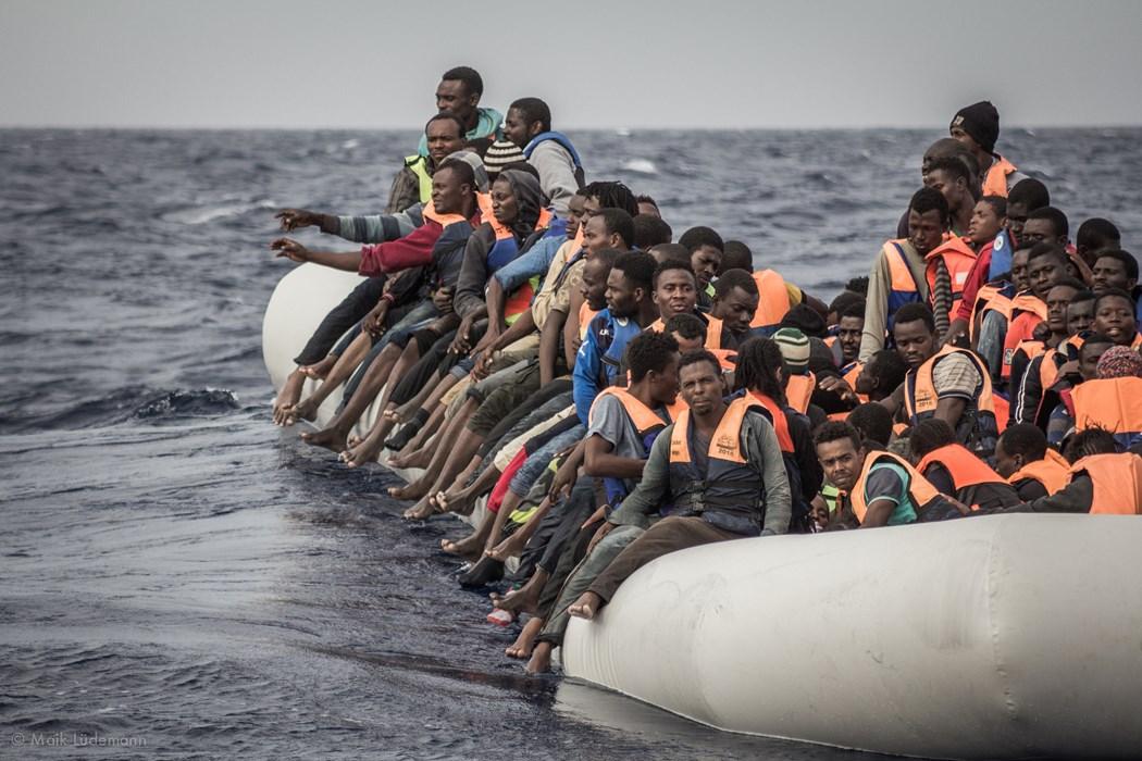 """Geflüchtete auf einem völlig überfüllten Rettungsboot vor der libyschen Küste. Die Rettungswesten erhielten sie erst von der Crew der """"Minden""""."""