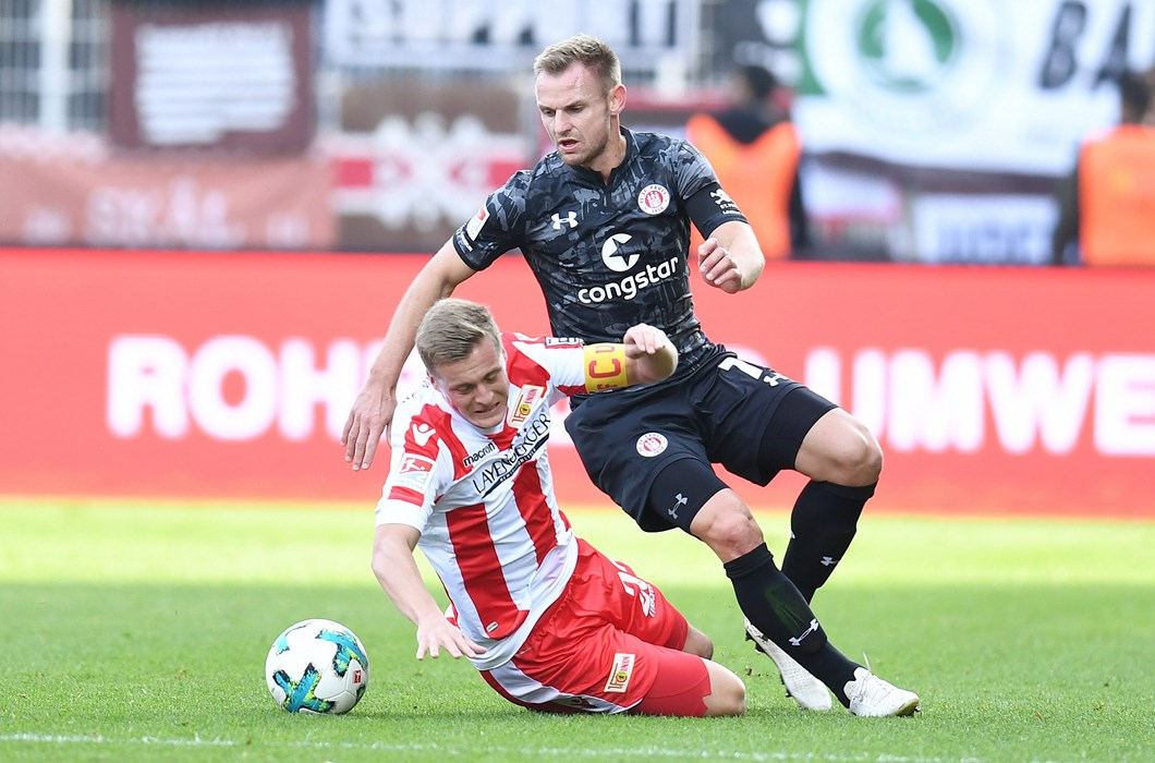 Captains Felix Kroos and Bernd Nehrig battle for the ball in a hard-fought contest.