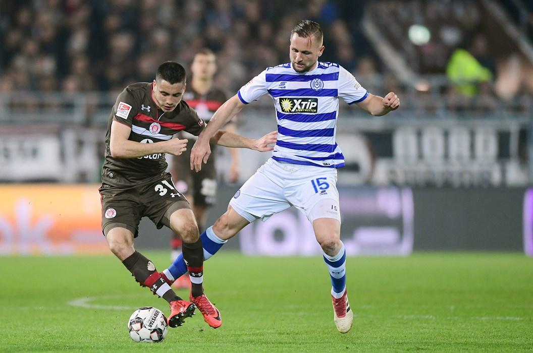 Ersin Zehir under challenge from former St. Pauli man John Verhoek.