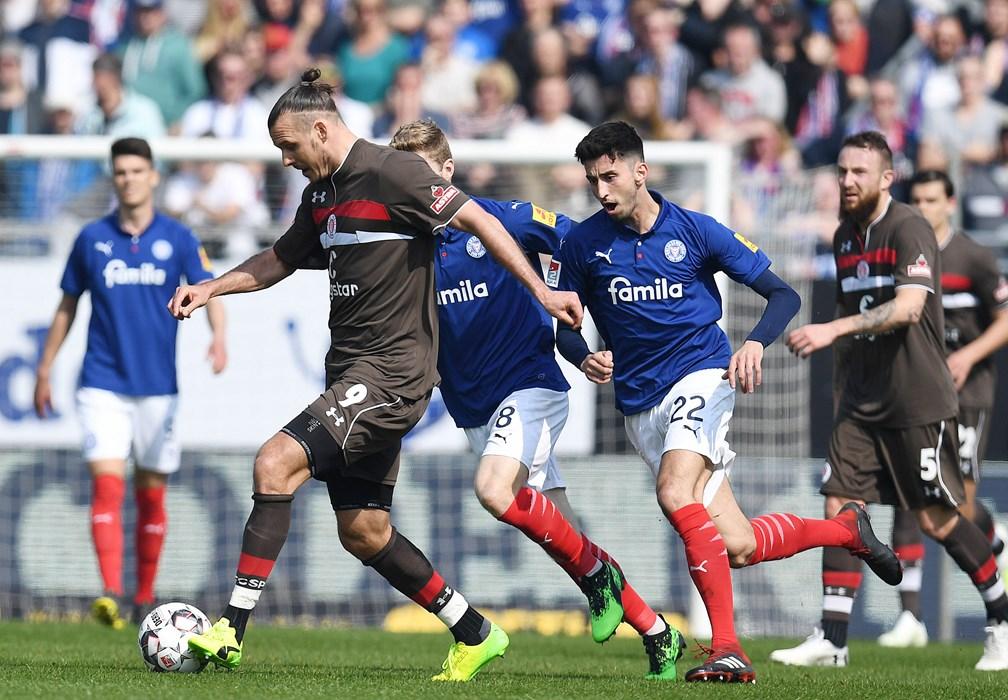 Goalscorer Alex Meier shields the ball from Kiel's Alexander Mühling (8) and Atakan Karazor (22).
