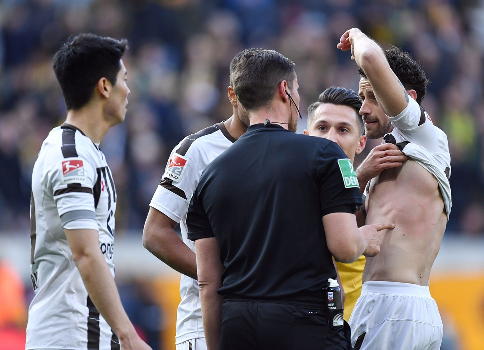 Jan-Philipp Kalla shows referee Robert Kempter the mark left by the ball on his upper body.