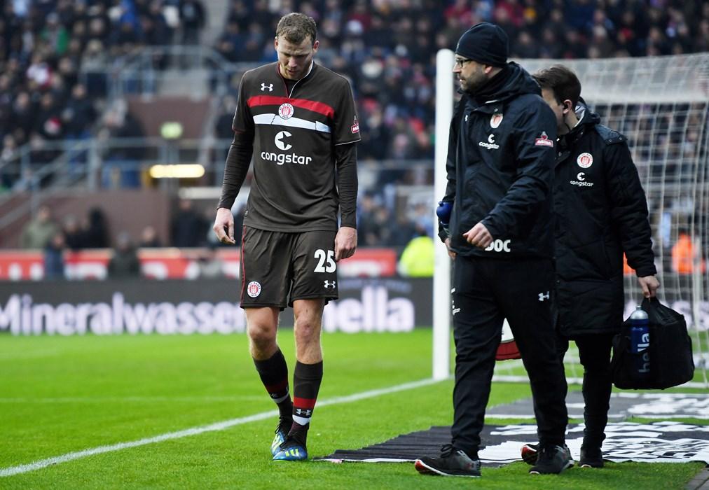 Henk Veerman wird kurz nach seiner Auswechslung von Mannschaftsarzt Dr. Sebastian Schneider und Physiotherapeut Mike Muretic begleitet.