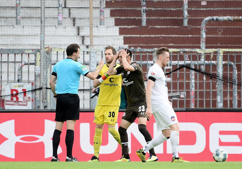 The main talking point in the first half: referee Lasse Koslowski (left) awards a penalty to the consternation of Johannes Flum (centre right).